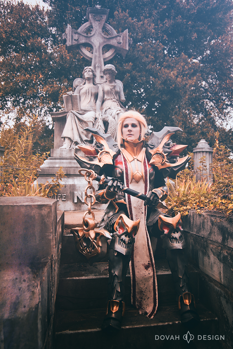 "Diablo 3 Crusader cosplay, ""Armor of Akkhan."" Costume is worn by Samantha, sitting on the steps of an oversized gravestone with two carved angels and cross. Holding Justinian's Mercy flail with both hands."
