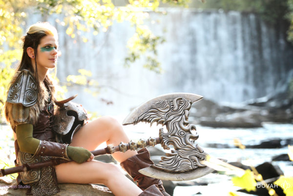 Skyrim Ancient Nord Armor cosplay, sitting on rock in front of waterfall, holding helmet and the rueful axe, looking out toward the distance.