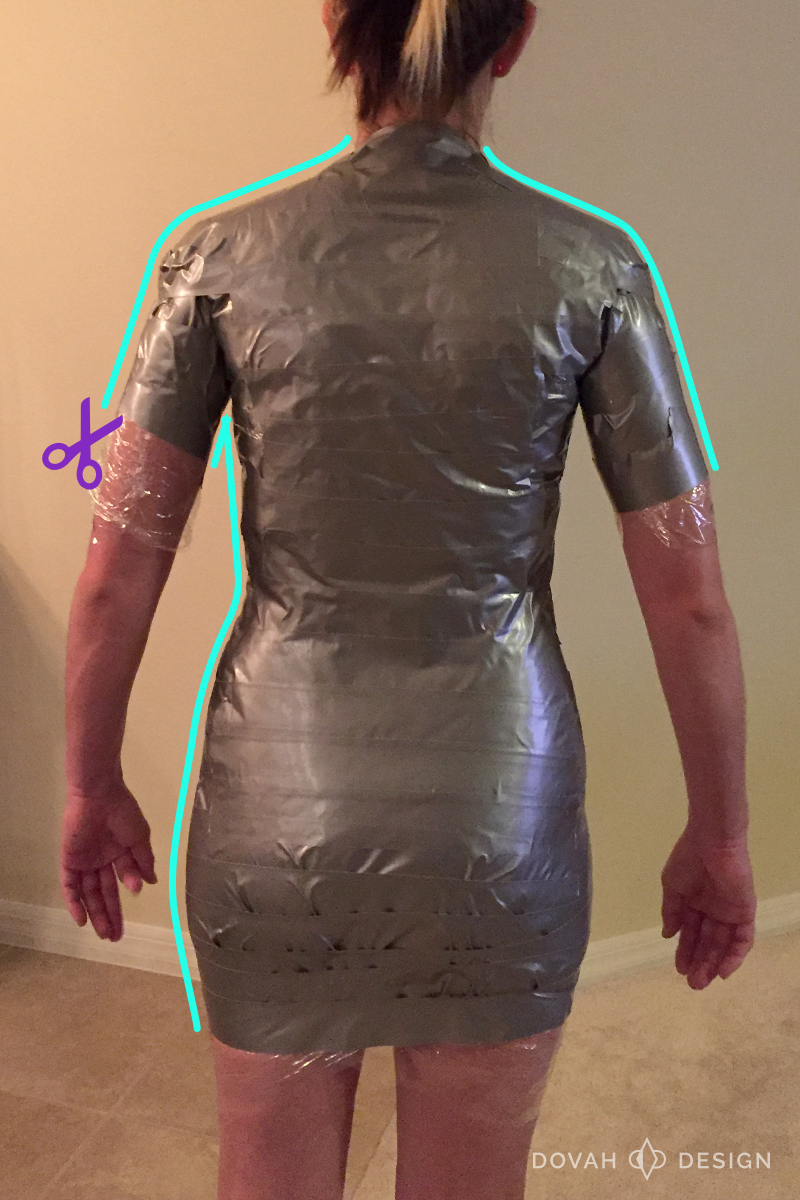 Sam from the back, fully wrapped in duct tape. Diagram markings show where the cut lines should be on duct tape. Left neck down to arm, left armpit down to leg, right neck down to arm.