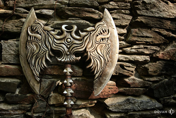 Skyrim Rueful Axe, leaned up against an old stone wall, one side glowing in a beam of sunlight.
